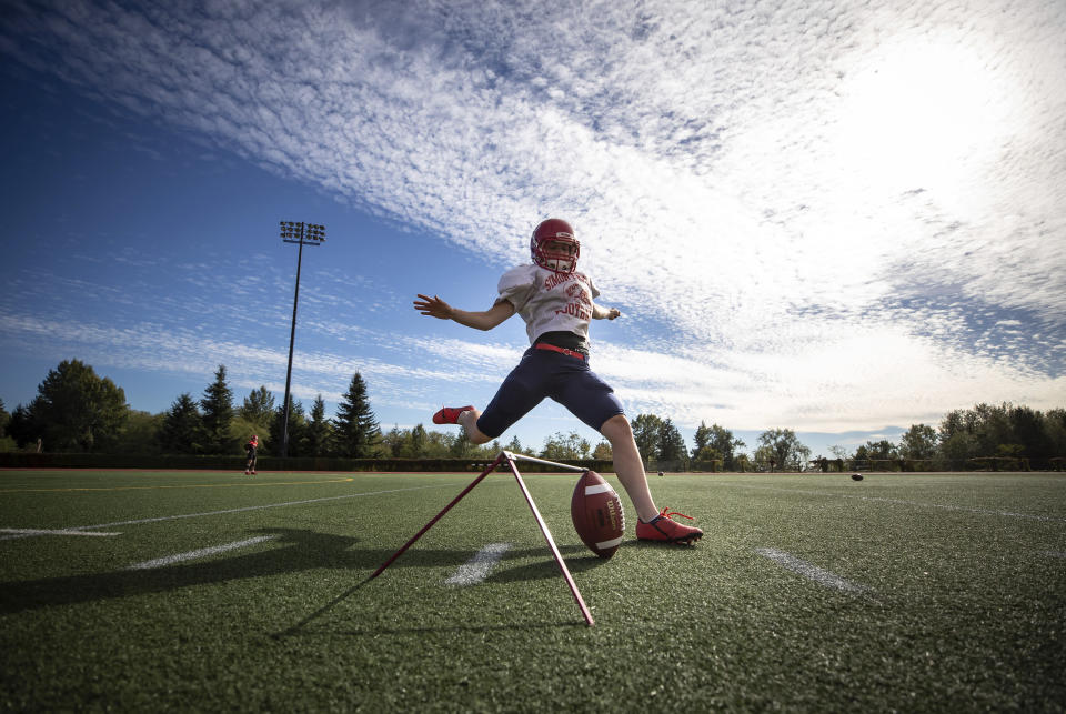Simon Fraser University football team kicker Kristie Elliott, kicks a ball while posing for a photograph before practice in Burnaby, B.C., Tuesday, Sept. 21, 2021. The 21-year-old Elliott booted a pair of successful conversions against Oregon's Linfield University on Sept. 11, becoming the first Canadian woman to play in — and score in — an NCAA football game. (Darryl Dyck/The Canadian Press via AP)