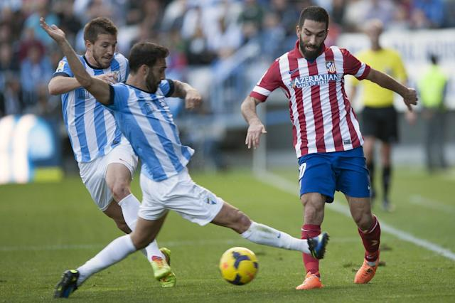 Atletico de Madrid's Arda Turan from Turkey, right, challenges for the ball with Malaga's Jesus Gamez, center, during a Spanish La Liga soccer match between Malaga and Atletico de Madrid at the La Rosaleda stadium in Malaga, Spain, Saturday, Jan. 4, 2014. (AP Photo/Daniel Tejedor)