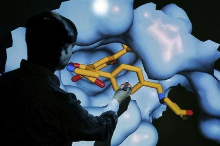Scientist Nathan Brown moves a 3D model of a HSP90 protein on a screen at the Institute of Cancer Research in Sutton, July 15, 2013. REUTERS/Stefan Wermuth