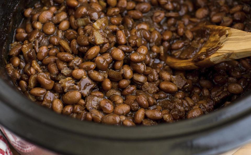 """<p>If you're going to a cookout, baked beans are an absolute must-have. This recipe uses a slow cooker to make the sauce extra thick and fragrant from the mix of bacon, brown sugar, molasses, mustard, garlic and cinnamon.</p> <p><a href=""""https://www.thedailymeal.com/best-recipes/slow-cooker-baked-beans-with-bacon?referrer=yahoo&category=beauty_food&include_utm=1&utm_medium=referral&utm_source=yahoo&utm_campaign=feed"""" rel=""""nofollow noopener"""" target=""""_blank"""" data-ylk=""""slk:For the Slow Cooker Baked Beans With Bacon recipe, click here."""" class=""""link rapid-noclick-resp"""">For the Slow Cooker Baked Beans With Bacon recipe, click here.</a></p>"""