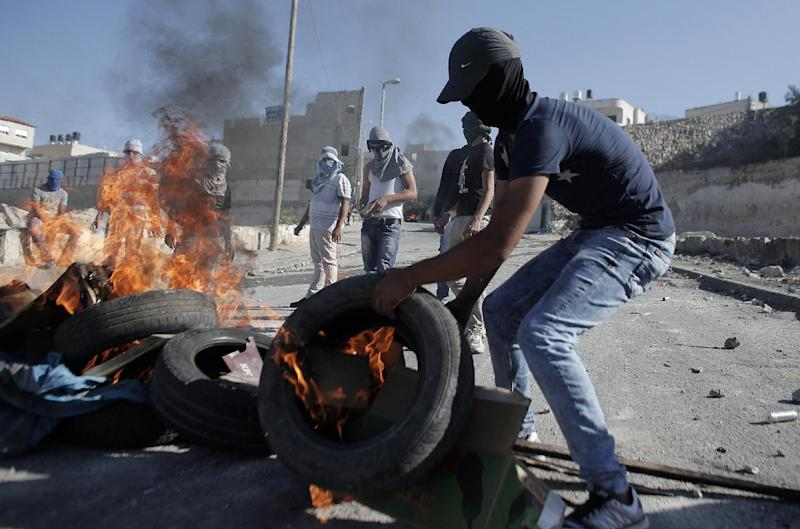 A Palestinian protester burns a tire during clashes with Israeli security officers in the Issawiya district of Arab east Jerusalem on October 24, 2014 (AFP Photo/Ahmad Gharabli)