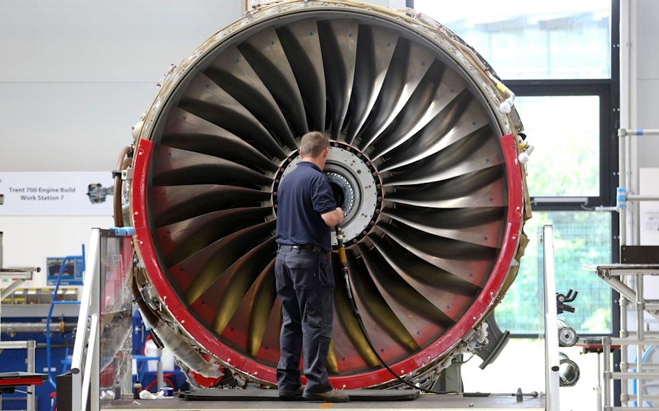 An employee works on a Trent 700 aircraft engine on the production line at the Rolls-Royce Holdings Plc factory in Derby - Bloomberg News/Chris Ratcliffe
