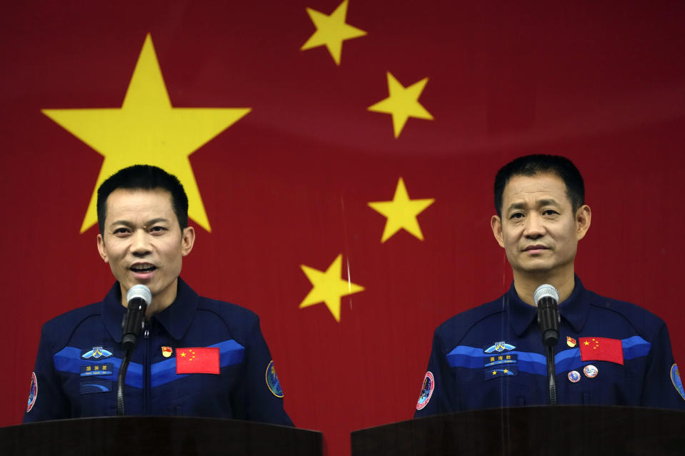 Chinese astronaut Tang Hongbo, left, speaks as fellow astronaut Nie Haisheng listens during a press conference at the Jiuquan Satellite Launch Center ahead of the Shenzhou-12 launch from Jiuquan in northwestern China, Wednesday, June 16, 2021. China plans on Thursday to launch three astronauts onboard the Shenzhou-12 spaceship, who will be the first crew members to live on China's new orbiting space station Tianhe, or Heavenly Harmony from the Jiuquan Satellite Launch Center in northwest China. (AP Photo/Ng Han Guan)