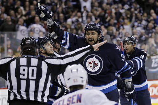 Winnipeg Jets' Dustin Byfuglien (33) arguest with a referee after they disallowed a Jets goal that went in after the buzzer blew at the end of second period of an NHL game in Winnipeg, Manitoba, Saturday, April 20, 2013. (AP Photo/The Canadian Press, John Woods)