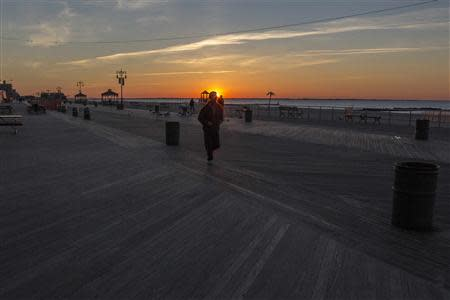 People walk on the Coney Island boardwalk as the sun peaks over the horizon in the Brooklyn borough of New York City, October 28, 2013. REUTERS/Brendan McDermid