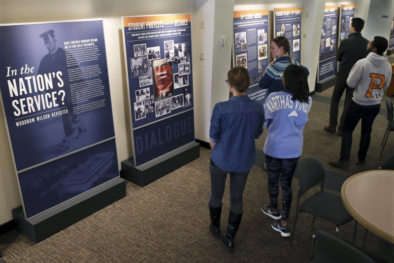 "FILE - In this April 3, 2016 file photo, Princeton University students walk through an exhibit titled, ""In the Nation's Service? Woodrow Wilson Revisited,"" at the Woodrow Wilson School of Public and International Affairs in Princeton, N.J. Princeton University on Saturday, June 27, 2020, has announced plans to remove the name of former President Woodrow Wilson from its public policy school because of his segregationist views, reversing a decision the Ivy League school made four years ago to retain the name. (AP Photo/Mel Evans)"