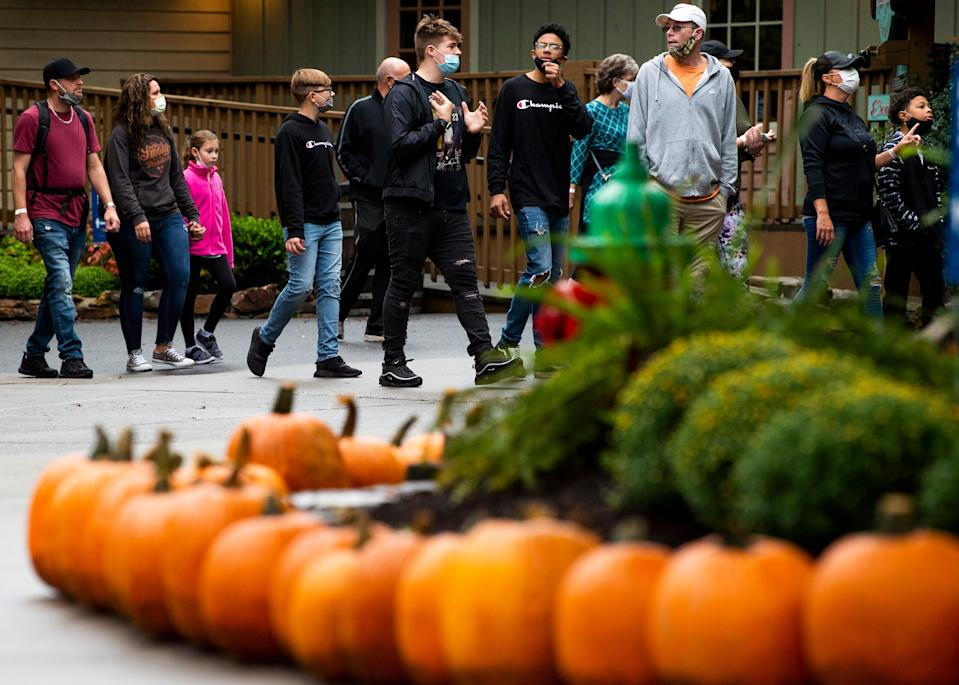 Dollywood guests walk through walkways lined with pumpkins as part of Dollywood's Harvest Festival on Friday, Sept. 25, 2020.