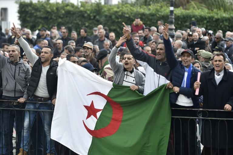 Algerian protesters shouted slogans supporting the upcoming elections near an anti-government demonstration in Algiers on December 9 (AFP Photo/RYAD KRAMDI                         )