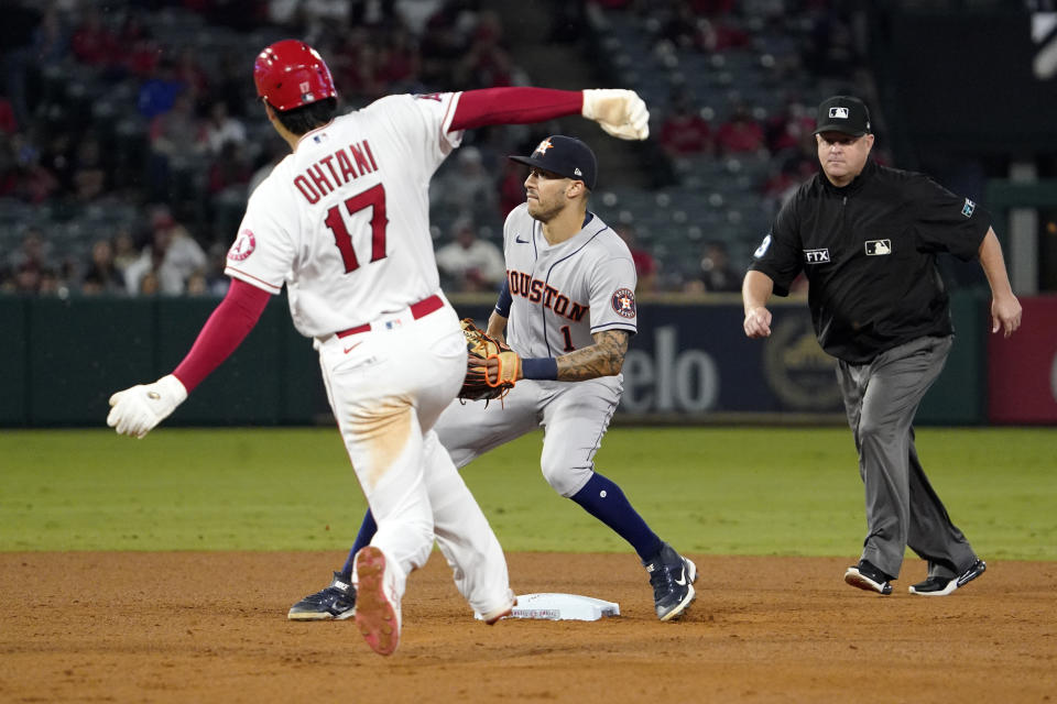 Los Angeles Angels designated hitter Shohei Ohtani, left, steals second as Houston Astros shortstop Carlos Correa, center, waits for the throw while second base umpire Todd Tichenor watches during the sixth inning of a baseball game Thursday, Sept. 23, 2021, in Anaheim, Calif. (AP Photo/Mark J. Terrill)