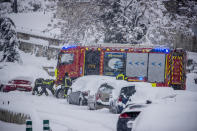 Firefighters work removing snow from a car during a heavy snowfall in Rivas Vaciamadrid, Spain, Saturday, Jan. 9, 2021. An unusual and persistent blizzard has blanketed large parts of Spain with snow, freezing traffic and leaving thousands trapped in cars or in train stations and airports that had suspended all services as the snow kept falling on Saturday. The capital, Madrid, and other parts of central Spain activated for the first time its red weather alert, its highest, and called in the military to rescue people from cars vehicles trapped in everything from small roads to the city's major thoroughfares. (AP Photo/Manu Fernandez)