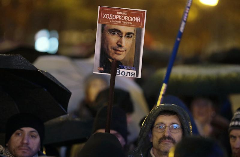 Demonstrators hold a portrait of jailed tycoon Mikhail Khodorkovsky during a protest rally in Moscow, Russia, Tuesday, Oct. 30, 2012. Several hundred people rallied in central Moscow Tuesday in support of jailed opposition activists. The rally, which was sanctioned by authorities, went on peacefully amid heavy police cordons. It attracted supporters of both leftist and liberal parties, who urged the government to release more than a dozen of people facing accusations over their involvement in an opposition protest in May that ended in clashes with police. (AP Photo/Mikhail Metzel)