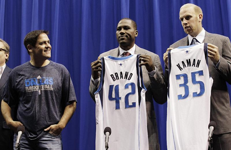 Dallas Mavericks owner Mark Cuban, left, watches as recent team additions Elton Brand (42) and Chris Kaman (35) show their new jerseys during an NBA basketball news conference introducing them at American Airlines Center in Dallas, Monday, Sept. 10, 2012. (AP Photo/LM Otero)