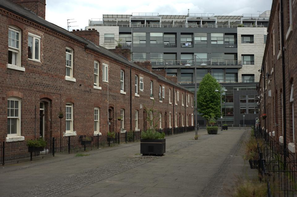 A residential street on November 27, 2014, in Manchester city centre on which are two rows of terraced houses. At the end of the row is a multi-storey block of modern flats. (Photo by Jonathan Nicholson/NurPhoto) (Photo by NurPhoto/NurPhoto via Getty Images)
