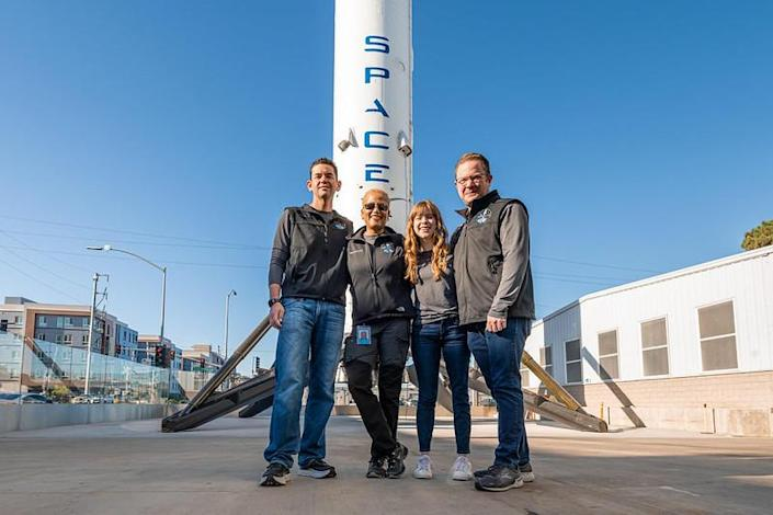 The crew poses in front of a SpaceX Falcon 9 first stage booster on display at company headquarters in Hawthorne, California. / Credit: Inspiration4