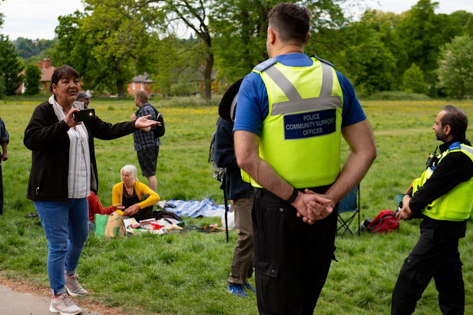 Police monitor a gathering of people at Highbury Park in Birmingham, after the introduction of measures to bring the country out of lockdown.