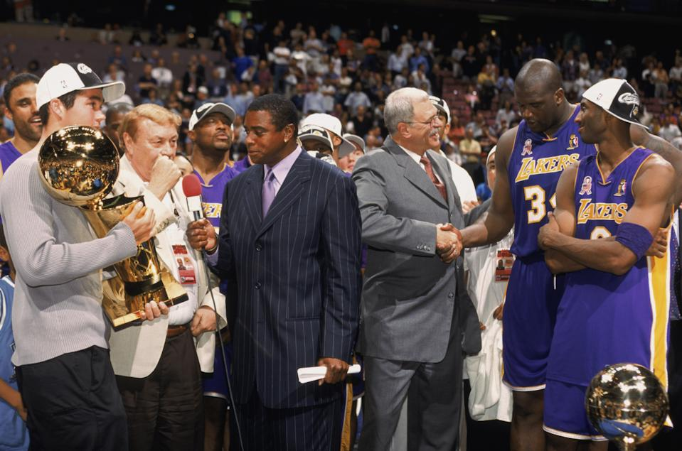 Head coach Phil Jackson of the Los Angeles Lakers congratulates guard Kobe Bryant #8 and center Shaquille O'Neal #34 as broadcaster Ahmad Rashad of NBC interviews Lakers owner Dr. Jerry Buss after Game Four of the 2002 NBA Finals against the New Jersey Nets at Continental Airlines Arena in East Rutherford, New Jersey on June 12, 2002. The Lakers defeated the Nets 113-107 and won the series 4-0. (Photo by Noren Trotman/NBAE/Getty Images)