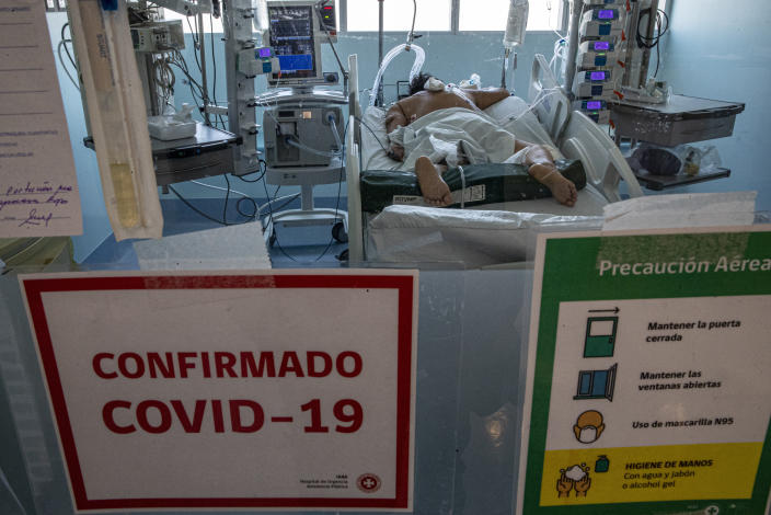 A COVID-19 patient lies in the ICU at the Posta Central Hospital in Santiago, Chile, Thursday, Dec. 24, 2020, on the same day the first shipment of coronavirus vaccines arrived from Pfizer and its German partner, BioNTech. (AP Photo/Esteban Felix)