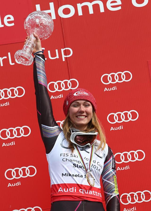 Mikaela Shiffrin, of the United States, holds her trophy for an alpine ski women's slalom, at the World Cup finals, in Lenzerheide, Switzerland, Saturday, March 15, 2014. (AP Photo/Armando Trovati)