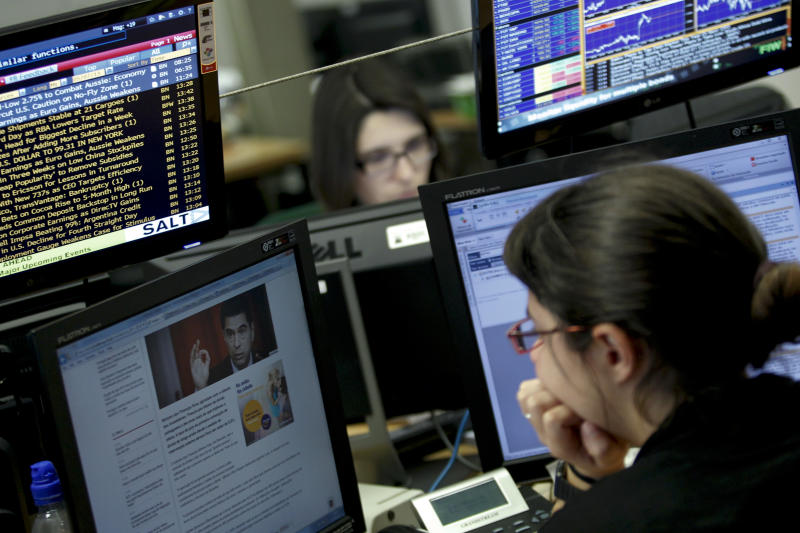 A broker watches a computer screen that shows a picture of Portugal's Finance Minister Vitor Gaspar while working in a trading room of a Portuguese bank in Lisbon, Tuesday, May 7, 2013. Portugal held a sale of its 10-year bonds on Tuesday for the first time since it needed a bailout in 2011, representing a milestone in its efforts to regain investor confidence and prove its contested austerity policies are paying off. (AP Photo/Francisco Seco)