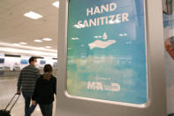 A hand sanitizer dispenser hangs in a concourse at Miami International Airport, Wednesday, Nov. 25, 2020, in Miami. (AP Photo/Lynne Sladky)