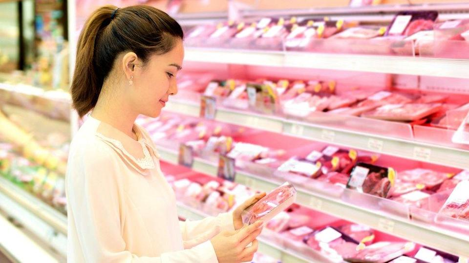 Woman buying meat in supermarket