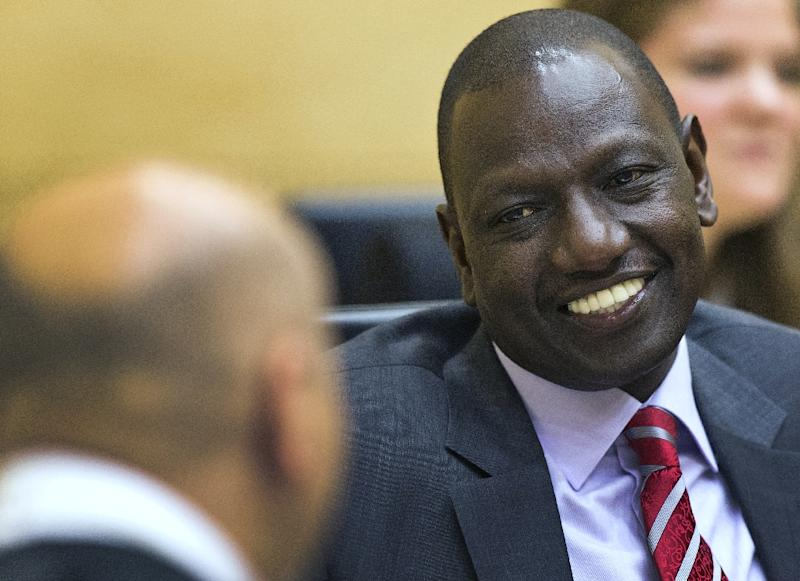 Kenya's Deputy President William Ruto speaks with his defense counsel before the start of his trial at the International Criminal Court in The Hague on September 10, 2013 (AFP Photo/Michael Kooren)