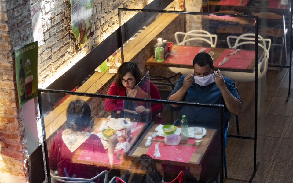People eat lunch at a restaurant with plastic dividers between tables, as a preventative measure amid the COVID-19 pandemic in Sao Paulo, Brazil, Monday, July 6, 2020. Bars, restaurants and beauty salons were allowed to re-open Monday after over three months of quarantine, but are required to observe preventative measures and reduced operating hours only during the day. (AP Photo/Andre Penner)
