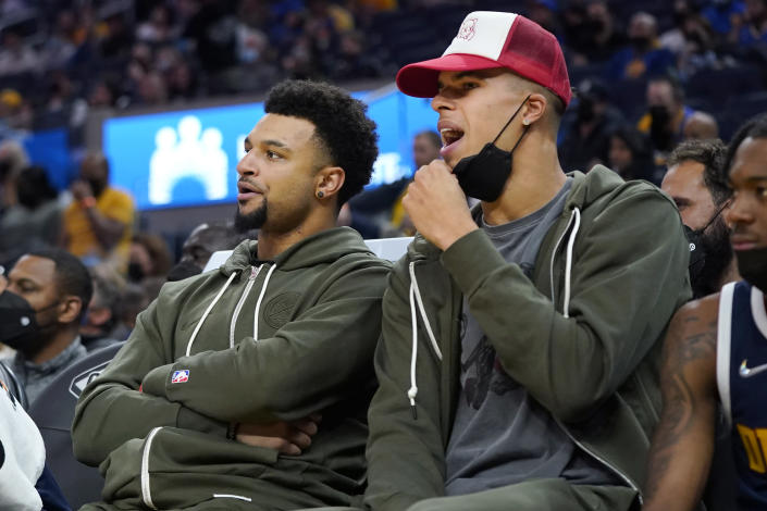 Denver Nuggets' Jamal Murray, left, and Michael Porter Jr. watch from the bench during the first half of the team's preseason NBA basketball game against the Golden State Warriors in San Francisco, Wednesday, Oct. 6, 2021. (AP Photo/Jeff Chiu)