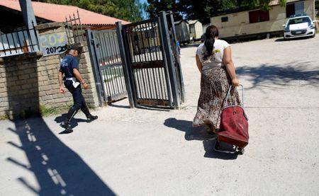 Municipal Policeman (L) and a Roma woman walk through an official Roma camp in Rome, Italy June 27, 2018. Picture taken June 27, 2018.  REUTERS/Tony Gentile