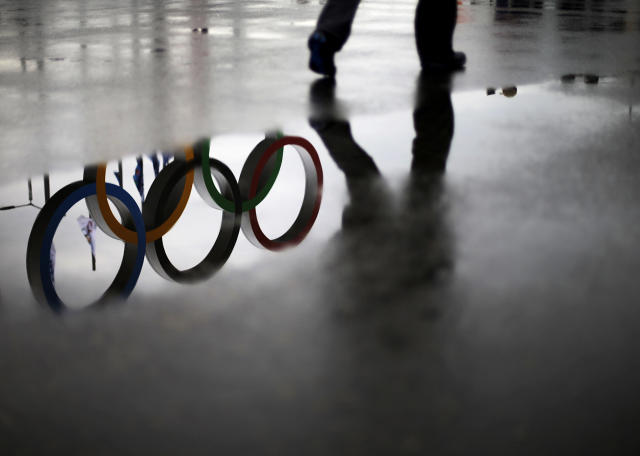 The Olympic rings are reflected in a puddle as a pedestrian strolls through Olympic Park at the 2014 Winter Olympics, Tuesday, Feb. 18, 2014, in Sochi, Russia. (AP Photo/David Goldman)