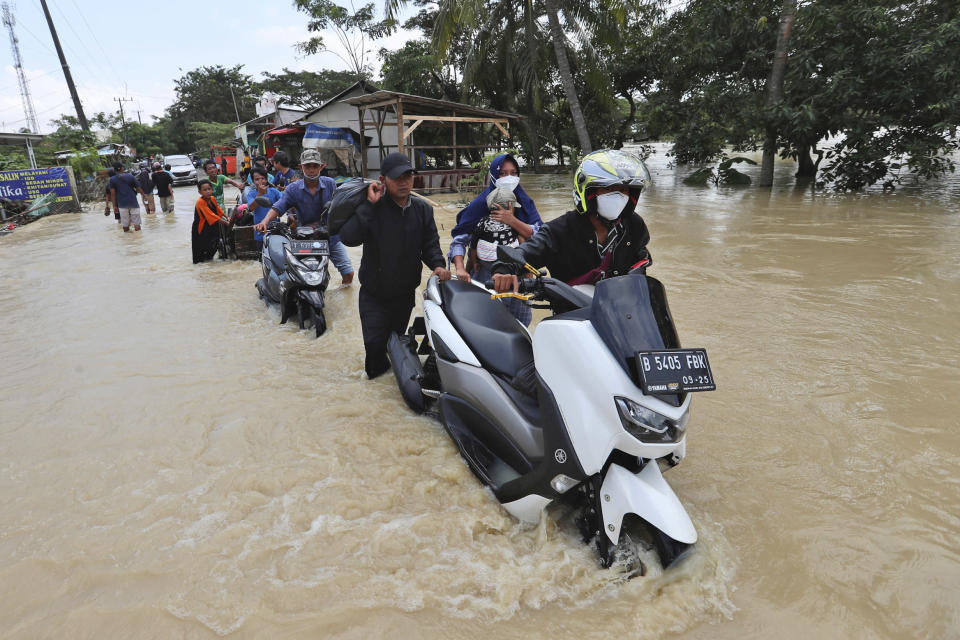 People push their motorcycles through a flooded area after the embankment of Citarum River burst, in Bekasi, Indonesia, Monday, Feb. 22, 2021. Heavy rains caused rivers to burst their banks in the region sending muddy water into residential and commercial areas, inundating thousands of homes. (AP Photo/Achmad Ibrahim)