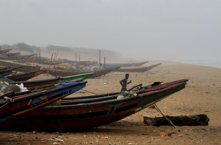 An Indian fisherman runs between the docked fishing boats amid strong winds at Chandrabhaga beach in Puri district of eastern Odisha state, India, Thursday, May 2, 2019. Hundreds of thousands of people were evacuated along India's eastern coast on Thursday as authorities braced for a cyclone moving through the Bay of Bengal that was forecast to bring extremely severe wind and rain. (AP Photo)