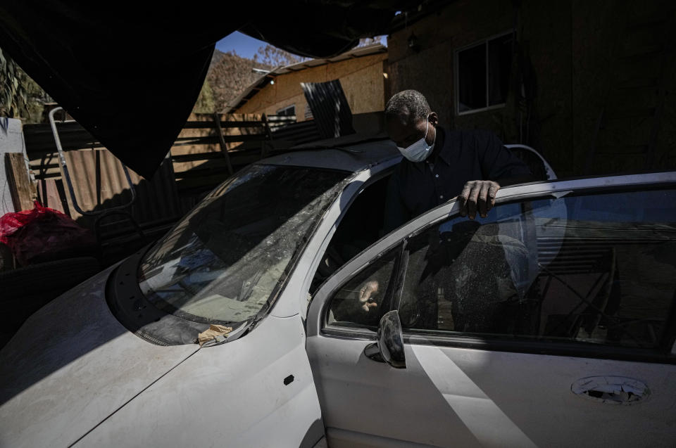"""Haitian Carlo Richard, whose Chilean identity card expired and has been rejected for renewal, repairs a car outside his home in the Dignidad camp in Santiago, Chile, Thursday, Sept. 30, 2021. """"What can I do? I can't do anything, (just) hold on until there is a change in our country so that we can return,"""" he said, referring to returning Haiti. (AP Photo/Esteban Felix)"""