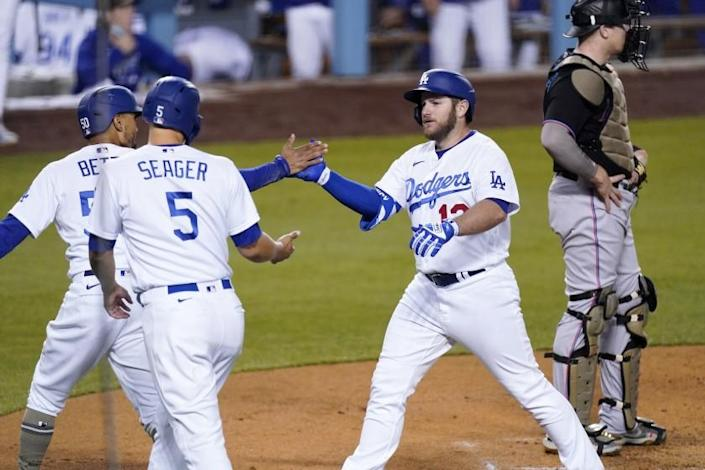 Los Angeles Dodgers' Max Muncy, second from right, is congratulated by Mookie Betts, left, and Corey Seager.