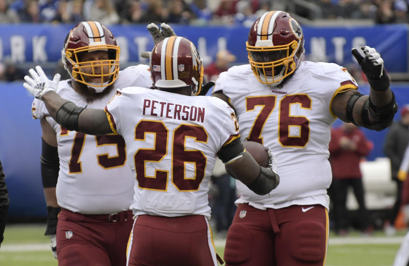 Washington Redskins running back Adrian Peterson (26) celebrates with offensive guard Brandon Scherff (75) and offensive tackle Morgan Moses (76) after scoring a touchdown against the New York Giants during the first quarter of an NFL football game, Sunday, Oct. 28, 2018, in East Rutherford, N.J. (AP Photo/Bill Kostroun)