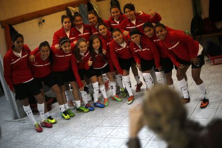 Players of the Colo Colo women's soccer club pose for a photo before a match in Santiago May 11, 2014.REUTERS/Ivan Alvarado