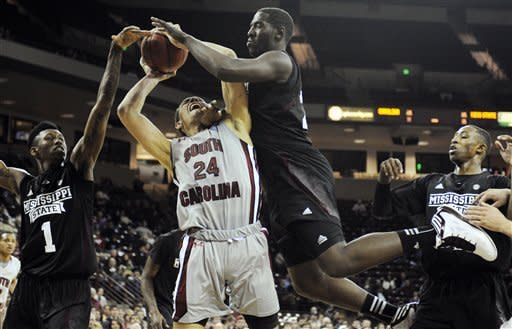 South Carolina's Michael Carrera (24) is fouled as he drives to the basket while Mississippi State's Gavin Ware (20) and Fred Thomas (1) defend during the first half of their NCAA college basketball game, Wednesday, March 6, 2013, in Columbia, S.C. (AP Photo/Mary Ann Chastain)