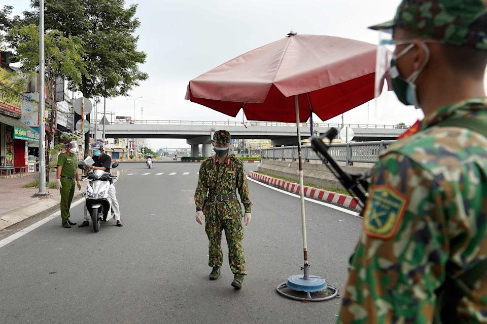 Vietnamese military personnel stand guard at a checkpoint in Ho Chi Minh City (AFP via Getty Images)