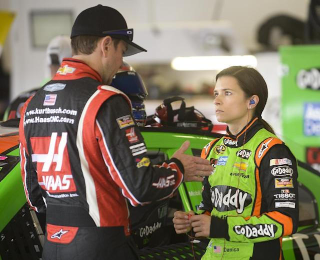 Kurt Busch, left, talks with Danica Patrick in the garage before a practice session for the Daytona 500 NASCAR Sprint Cup Series auto race at Daytona International Speedway in Daytona Beach, Fla., Friday, Feb. 21, 2014. (AP Photo/Phelan M. Ebenhack)