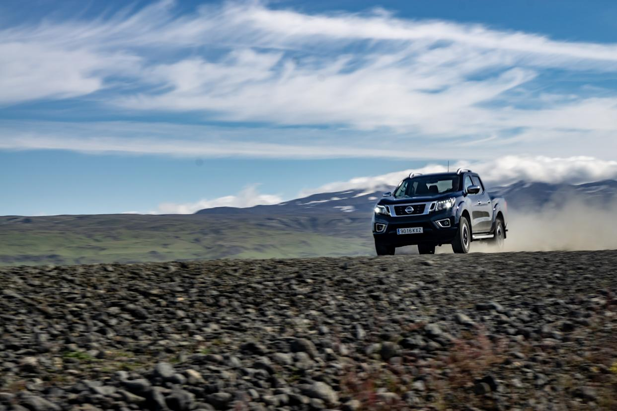 The Navara kicks up a huge plume of dust as it hammers along a track