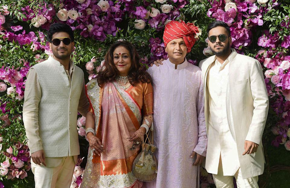 Indian businessman Anil Ambani (2nd R) poses for photographs along with his wife and former Bollywood actress Tina Ambani (2nd L) and their sons, Anshul Ambani (R) and Anmol Ambani (L), as they arrive to attend the wedding ceremony of Akash Ambani, son of Indian Businessman Mukesh Ambani, in Mumbai on March 9, 2019. (Photo by SUJIT JAISWAL / AFP) (Photo by SUJIT JAISWAL/AFP via Getty Images)
