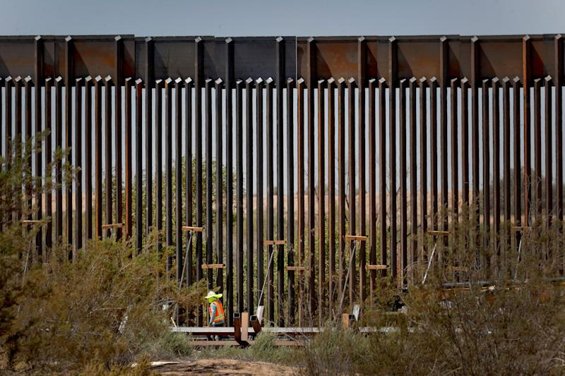 A government contractor walks beside a completed section of Pentagon-funded border wall along the Colorado River this month in Yuma, Ariz. (Photo: ASSOCIATED PRESS)