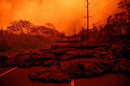 FILE PHOTO: Lava covers a road near Pahoa during ongoing eruptions of the Kilauea Volcano in Hawaii, U.S., June 8, 2018.  REUTERS/Terray Sylvester
