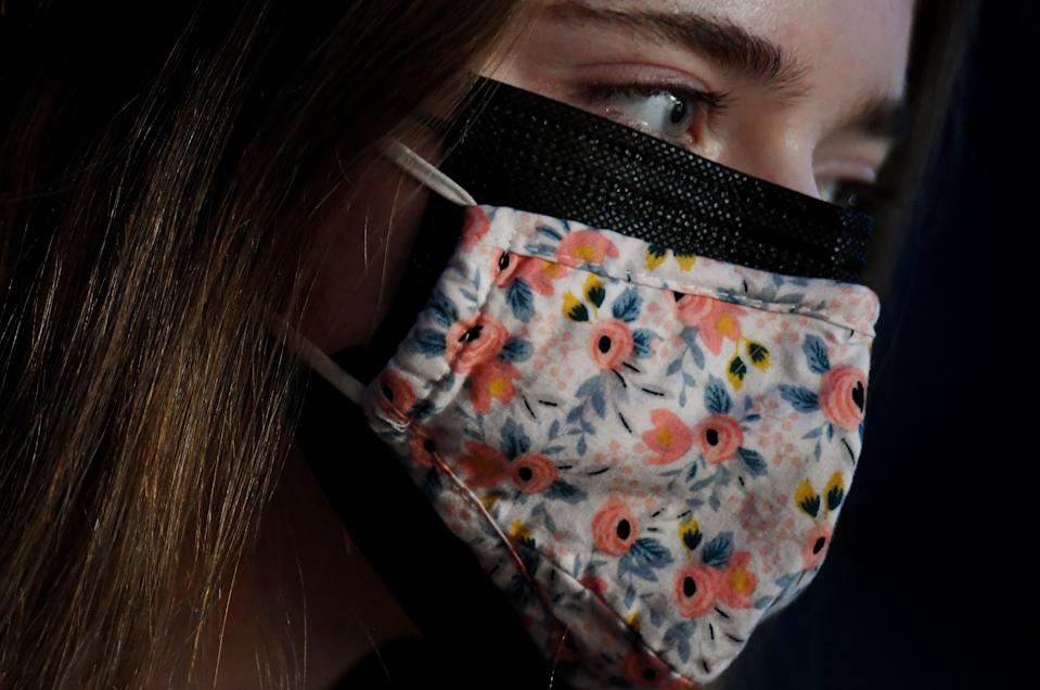 This illustration shows a woman wearing two facemasks, a cloth mask over a surgical mask, in Arlington, Virginia, on February 8, 2021. - As new, more transmissible variants of the coronavirus spread, experts say it's time to consider using a medical-grade respirator, or wearing a surgical and cloth mask together. Scientists have agreed for some time the main way the virus is spread is through the air, rather than surfaces, and there's growing evidence that small droplets from ordinary breathing and speech that can travel many meters (yards) are a common mode of transmission. (Photo by OLIVIER DOULIERY / AFP) (Photo by OLIVIER DOULIERY/AFP via Getty Images)
