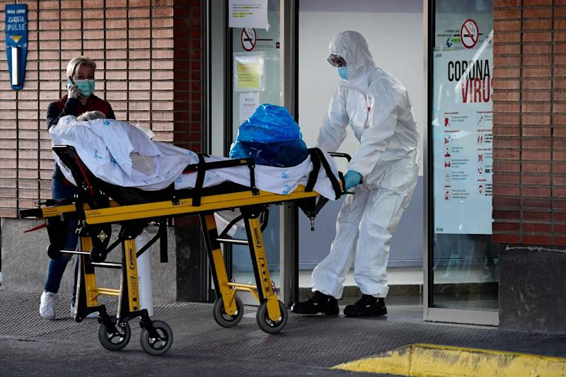 A health worker transfers a patient on a stretcher at the Severo Ochoa hospital in Leganes, Spain: AFP via Getty Images