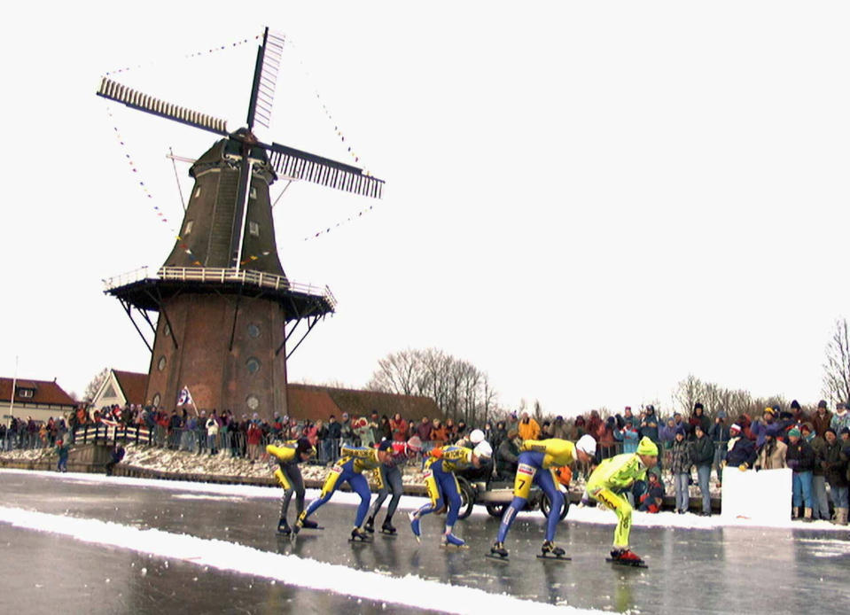 FILE - In this Saturday, Jan. 4, 1997, file image, skaters pass a windmill at the village of Birdaard, northern Netherlands, during the Elfstedentocht, or Eleven Towns Tour. The near-mythical Dutch speedskating race could fall victim to the coronavirus pandemic, even if the looming winter is cold enough to stage it for the first time in more than 20 years, organizers said Thursday Nov. 19, 2020. (AP Photo/Dimitri Georganas, File)