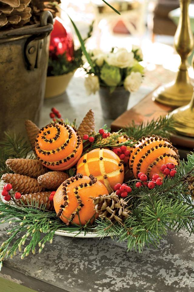 <p>Display pine boughs, pinecones and oranges dotted with cloves on a silver tray for an easy but eye-catching centerpiece.</p>