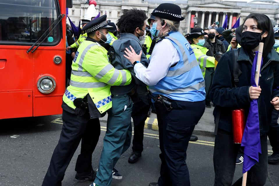 Police officers move a protester from the road in Trafalgar Square during protests on SaturdayREUTERS