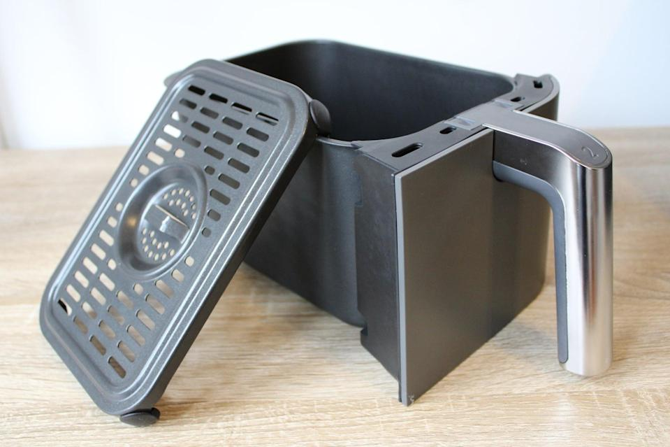 <p>If your air fryer has a removable crisper plate, take it out before cleaning, as you'll be washing it separately. Now is also a good time to use a rubber spatula to scrape off any remaining food.</p> <p>If your air fryer basket is in seriously messy shape, it can help to soak it before scrubbing it out. However, if you have greasy food, such as melted cheese, stuck to the basket, make sure you remove that before soaking. Otherwise, the fat from the cheese will counteract the suds in your dish soap, and the soak won't be as effective.</p>