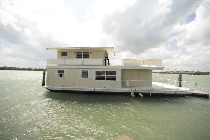 In this April 22, 2014 photo, Fane Lozman poses for photos holding his dog on his home floating in the waters near North Bay Village, Fla. Lozman caught legal lightning in a bottle last year when the U.S. Supreme Court agreed with him that his floating home was a house, not a vessel covered by maritime law. But the justices haven't had the last word: Lozman is still fighting for compensation for the home, which was destroyed years ago. The Fort Lauderdale-based federal judge whose decision on the floating home was overturned, U.S. District Judge William Dimitrouleas, refused earlier this year to give Lozman any of the $25,000 bond posted by the city of Riviera Beach to pay for Lozman's home in case he won. (AP Photo/J Pat Carter)